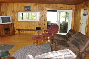 View of Living Room Toward Enclosed Porch and Lake.