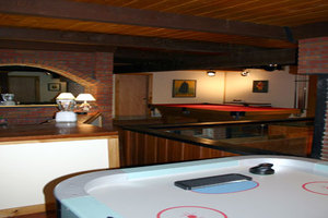 The 7\' air hockey table is located next to the wet bar