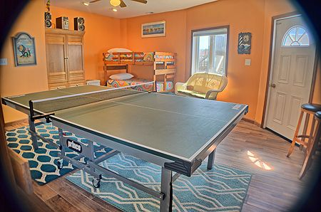 Bedroom 6 has a set of bunks and a ping pong table