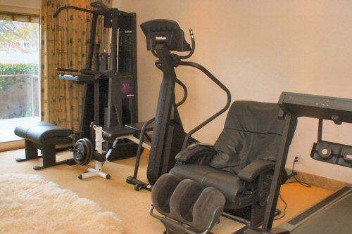 Workout room with Treadmill, massage chair and weights.