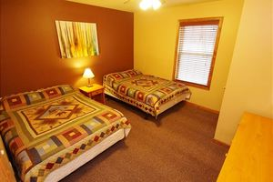 Bedroom with twin beds and carpeted flooring.