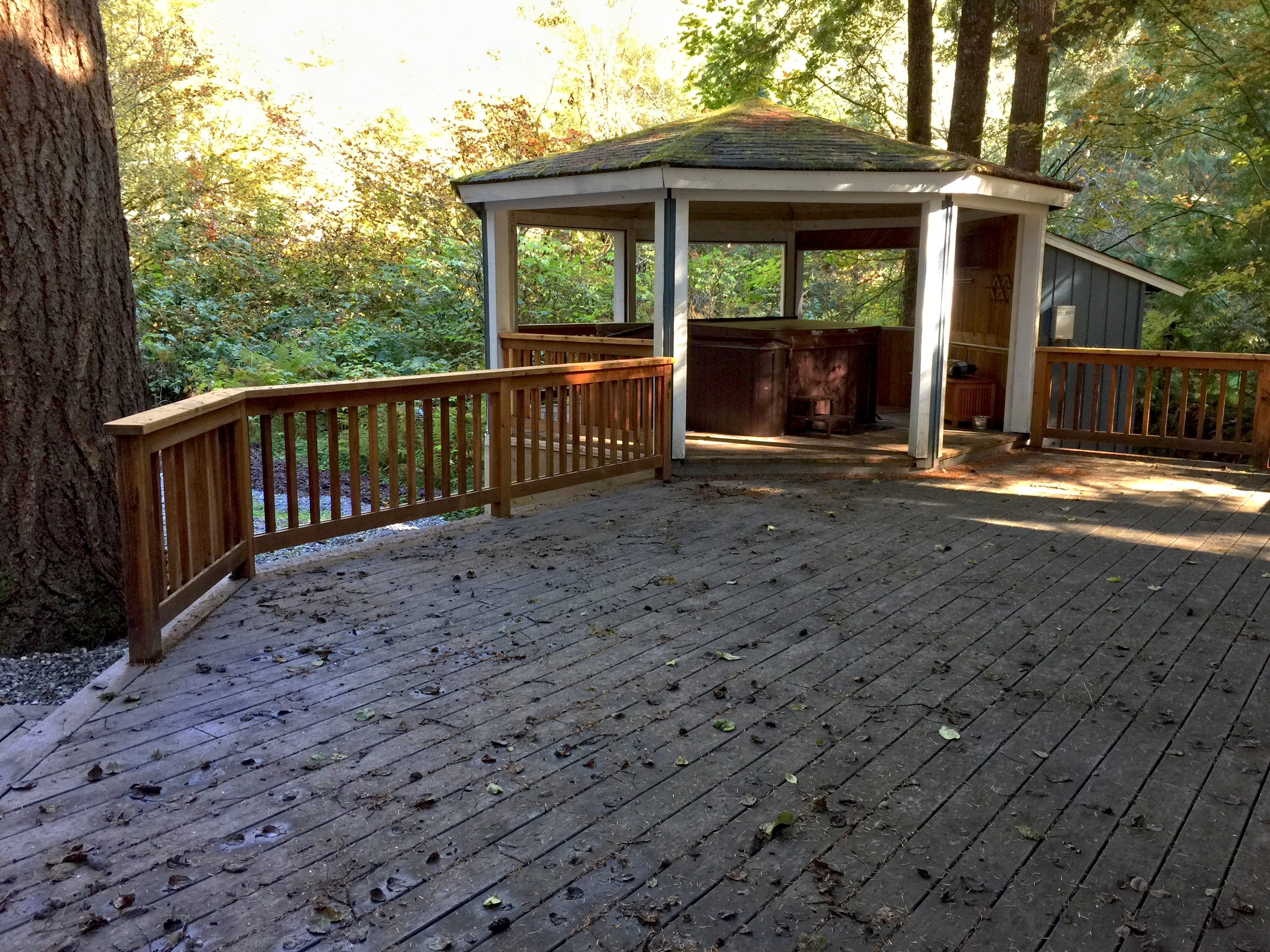 Large deck with a covered hot tub