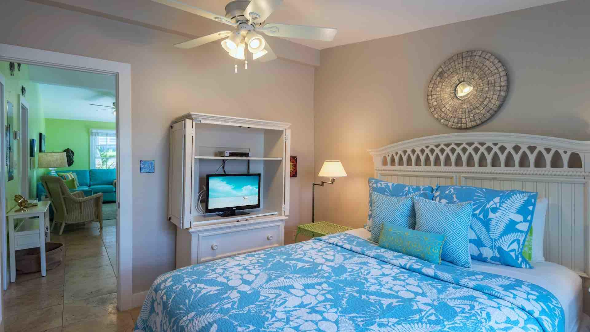 The second bedroom has an overhead fan and a flat screen TV...