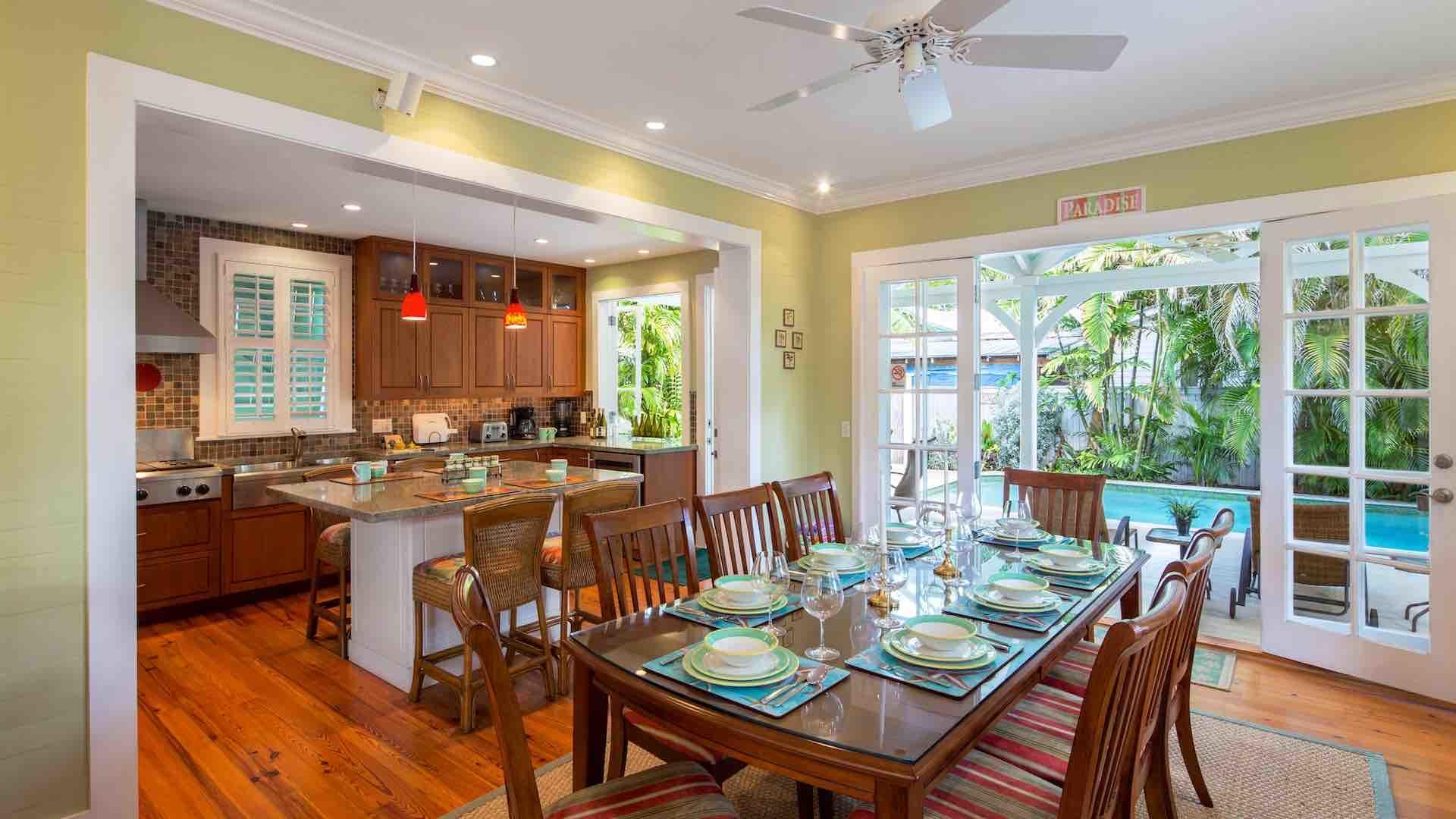 The dining room has four sets of French doors that open wide to the pool area…