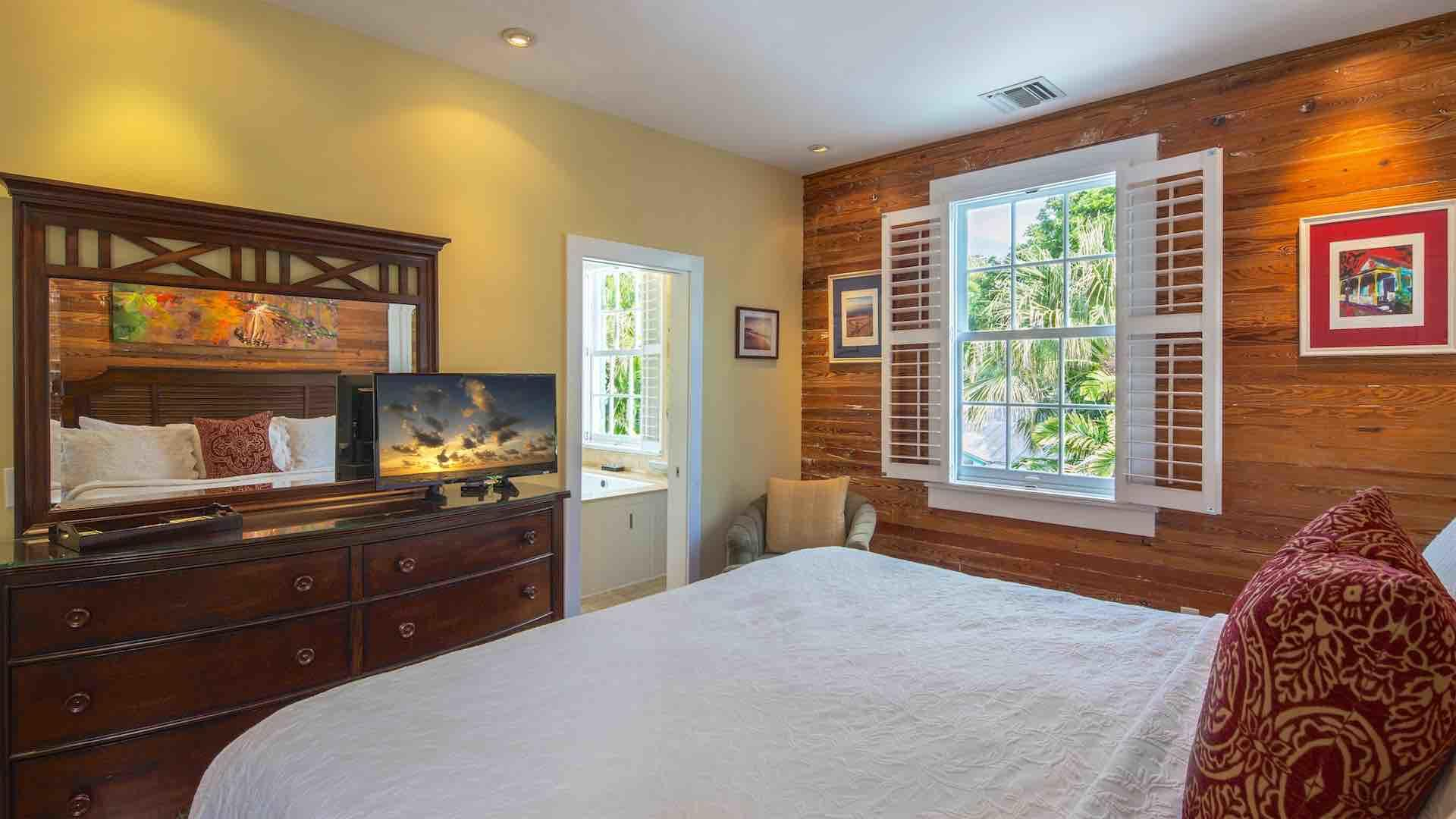 The master bedroom has more Dade County Pine, overhead fan and a flat screen TV…