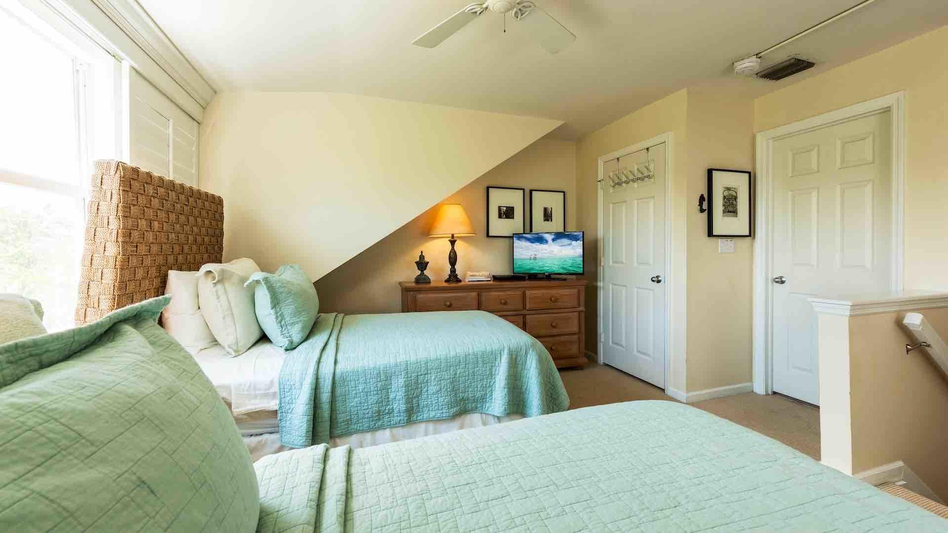 The second bedroom also has a flat screen TV, an overhead fan, and an en suite bathroom...