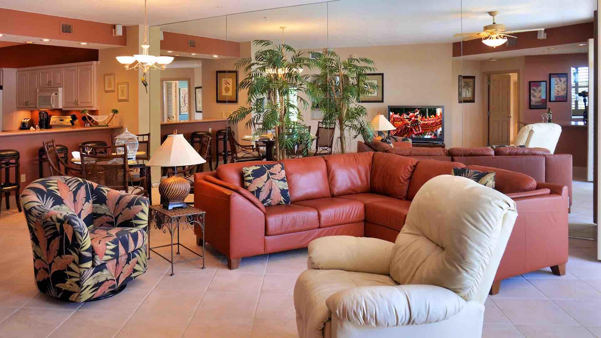 The living room has comfortable seating options, including a large sectional sofa...