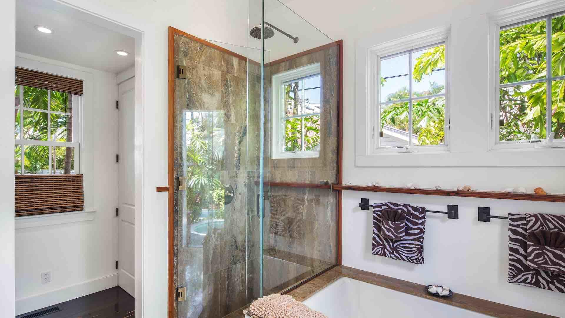 The master bathroom has a glass shower and deep tub...