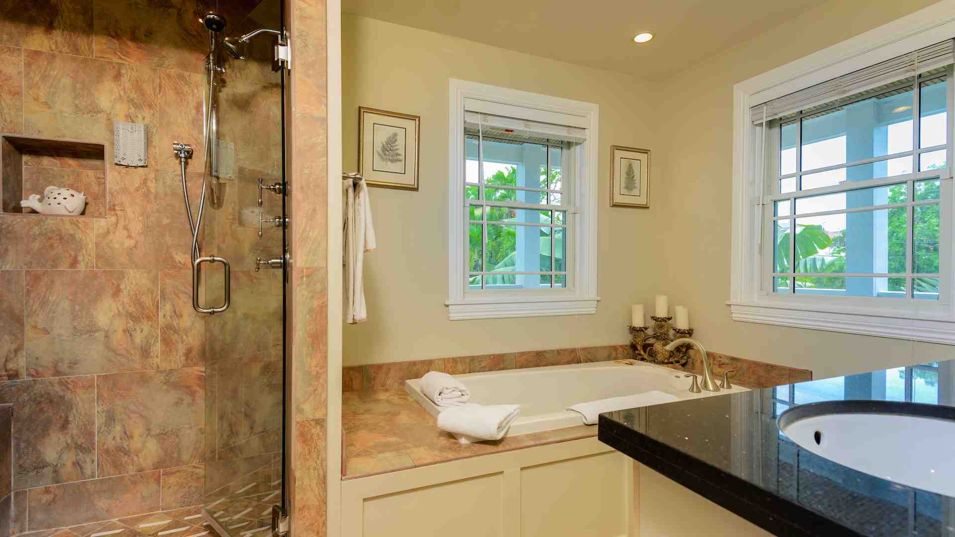 This full bathroom is directly attached to the first bedroom with glass shower...