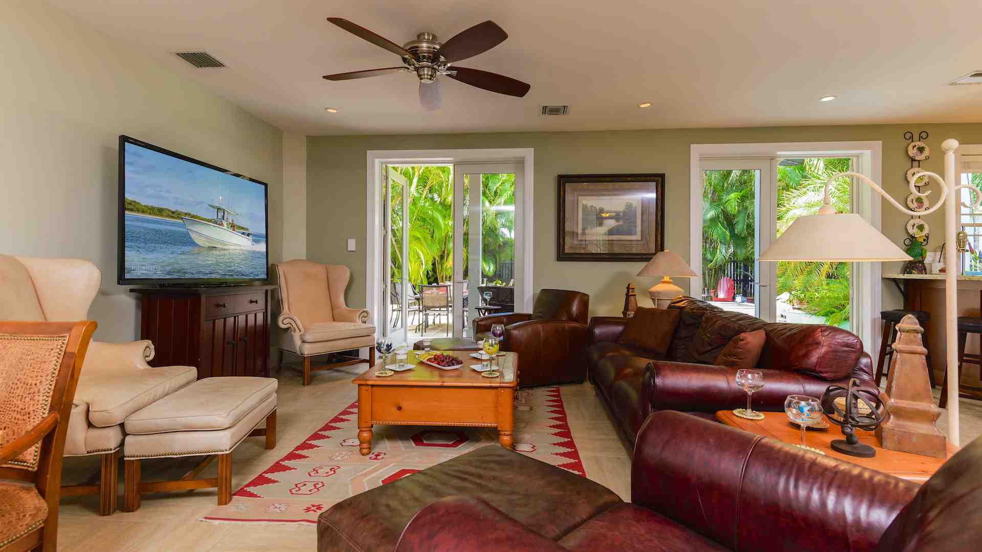 The main living area has several plush seating options including a leather couch...