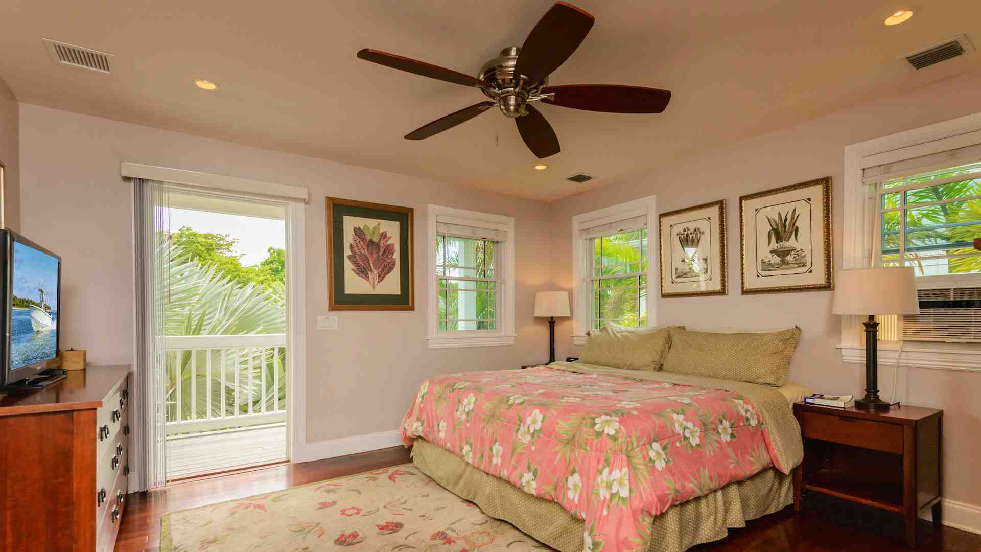 The master bedroom has a king sized bed, several large dressers, ceiling fan...