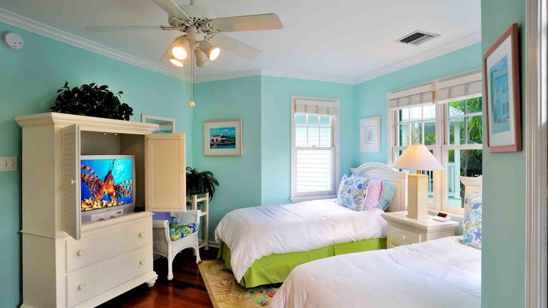 The second bedroom has a flat screen TV and an overhead fan...
