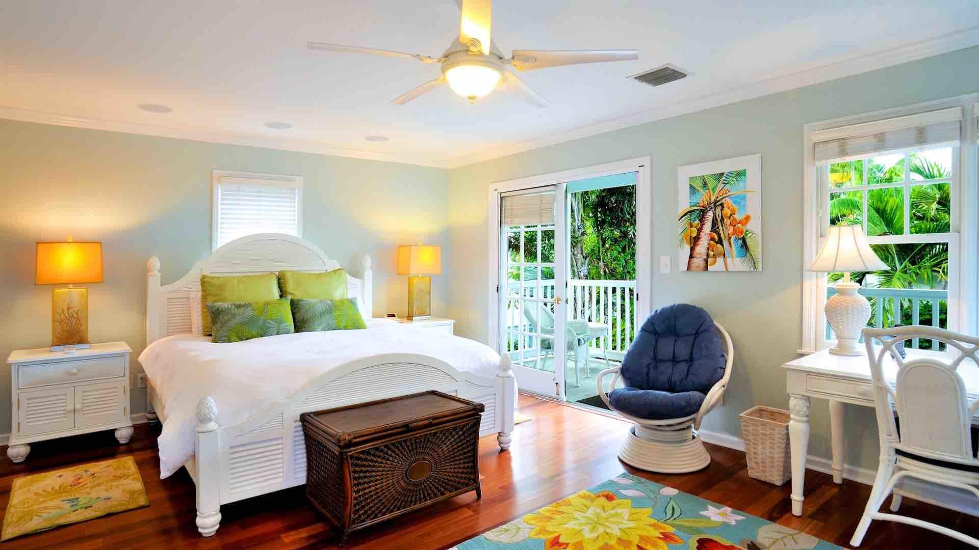 The master bedroom suite has two sets of French doors, king bed and ceiling fan...