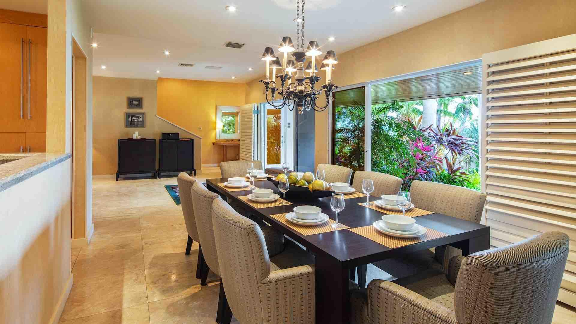 The formal dining room has a large dining table with eight upholstered chairs…