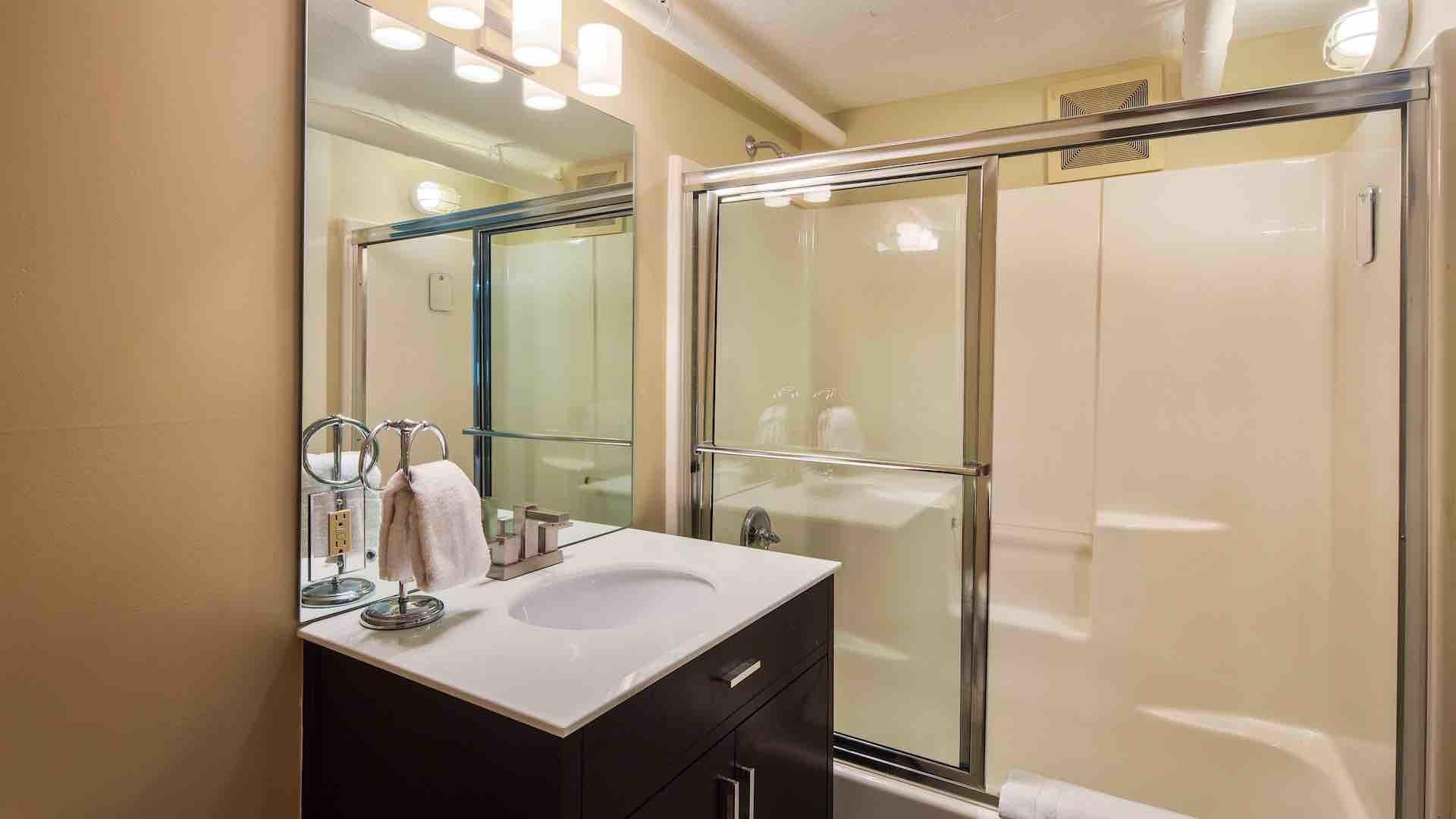The fourth bedroom's bathroom is also en suite, with pedestal sink and a shower…