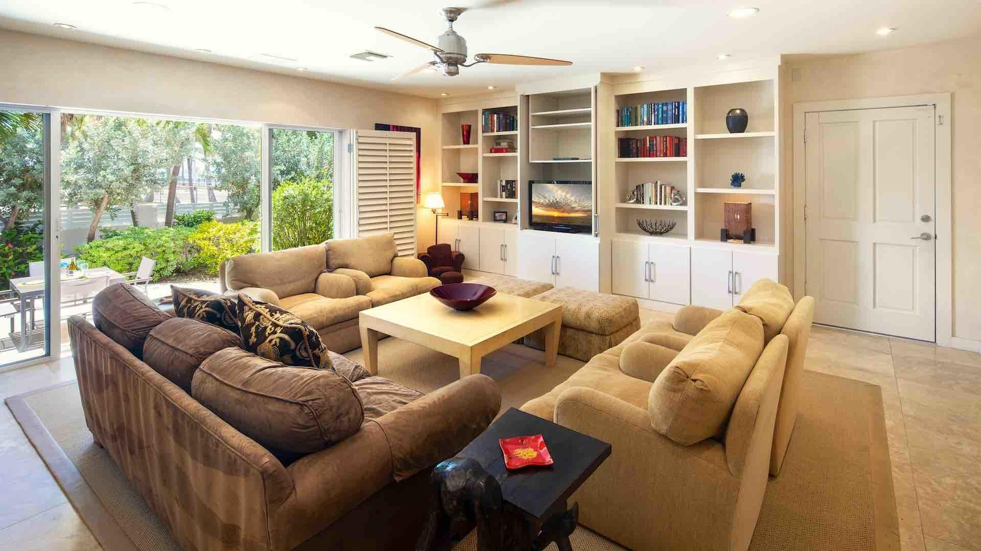 The living room has a large flat screen TV, overhead fan and large window wall…