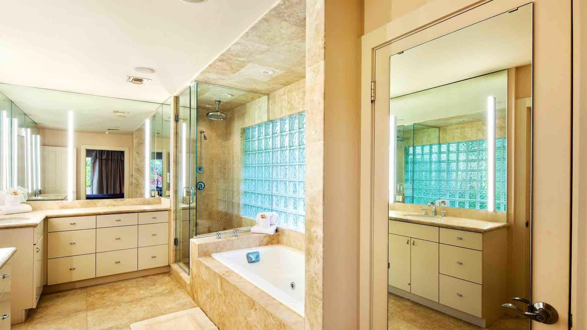 The first master bathroom is en suite with twin vanities, Jacuzzi & large shower
