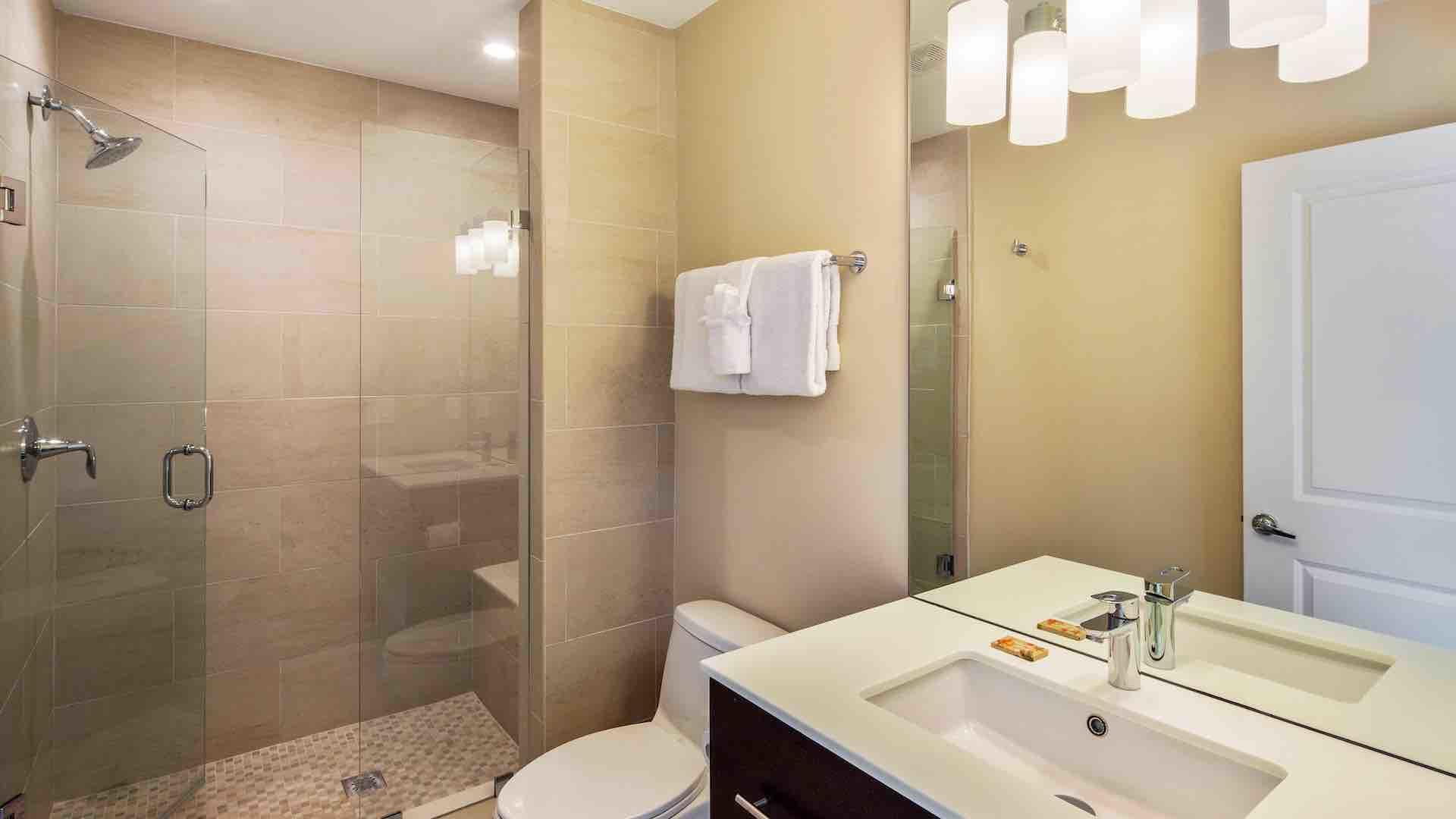 The second master bedroom has an en suite bathroom with frameless glass shower…