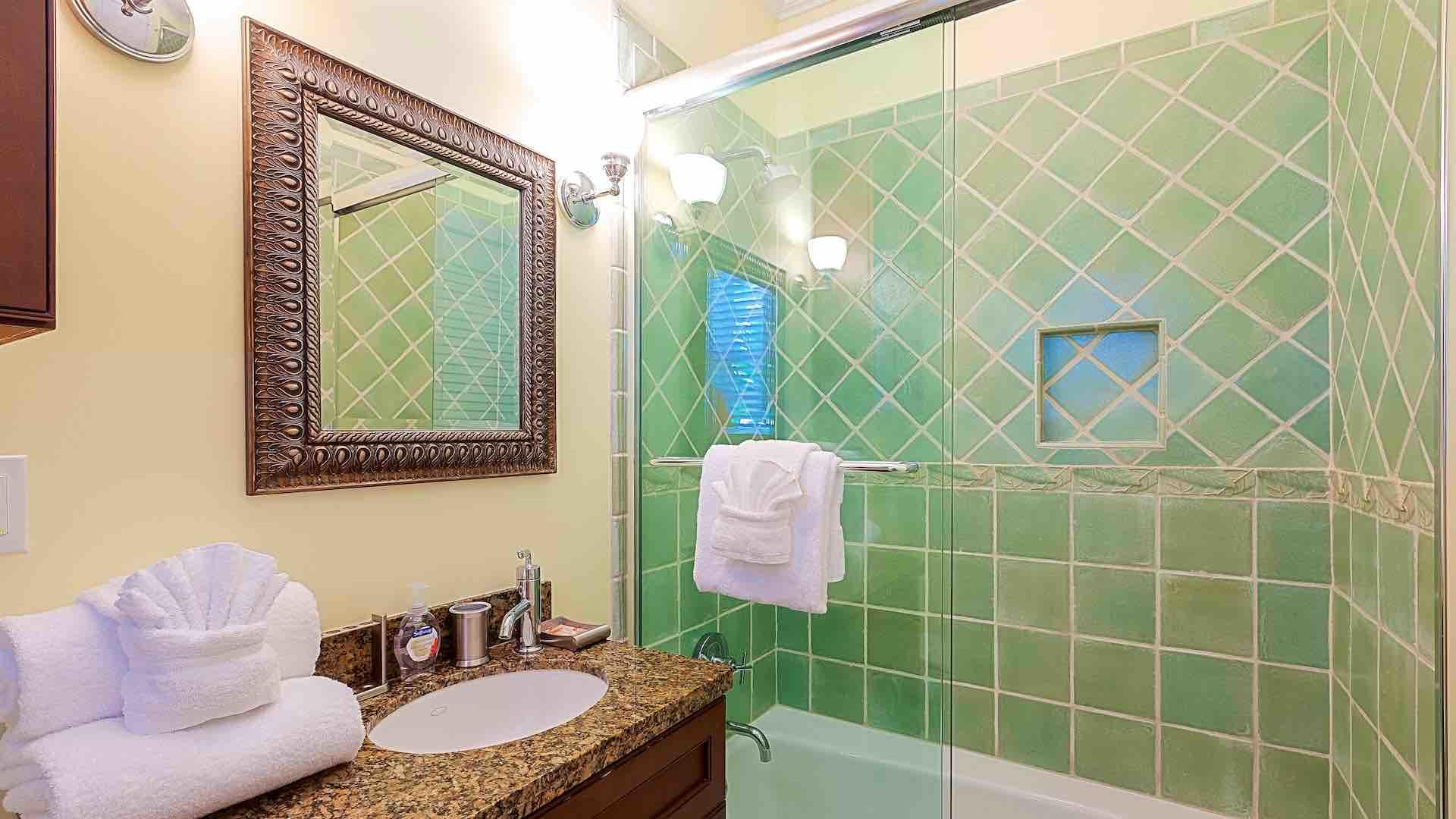 The en suite bathroom has a glass shower and tub combo...