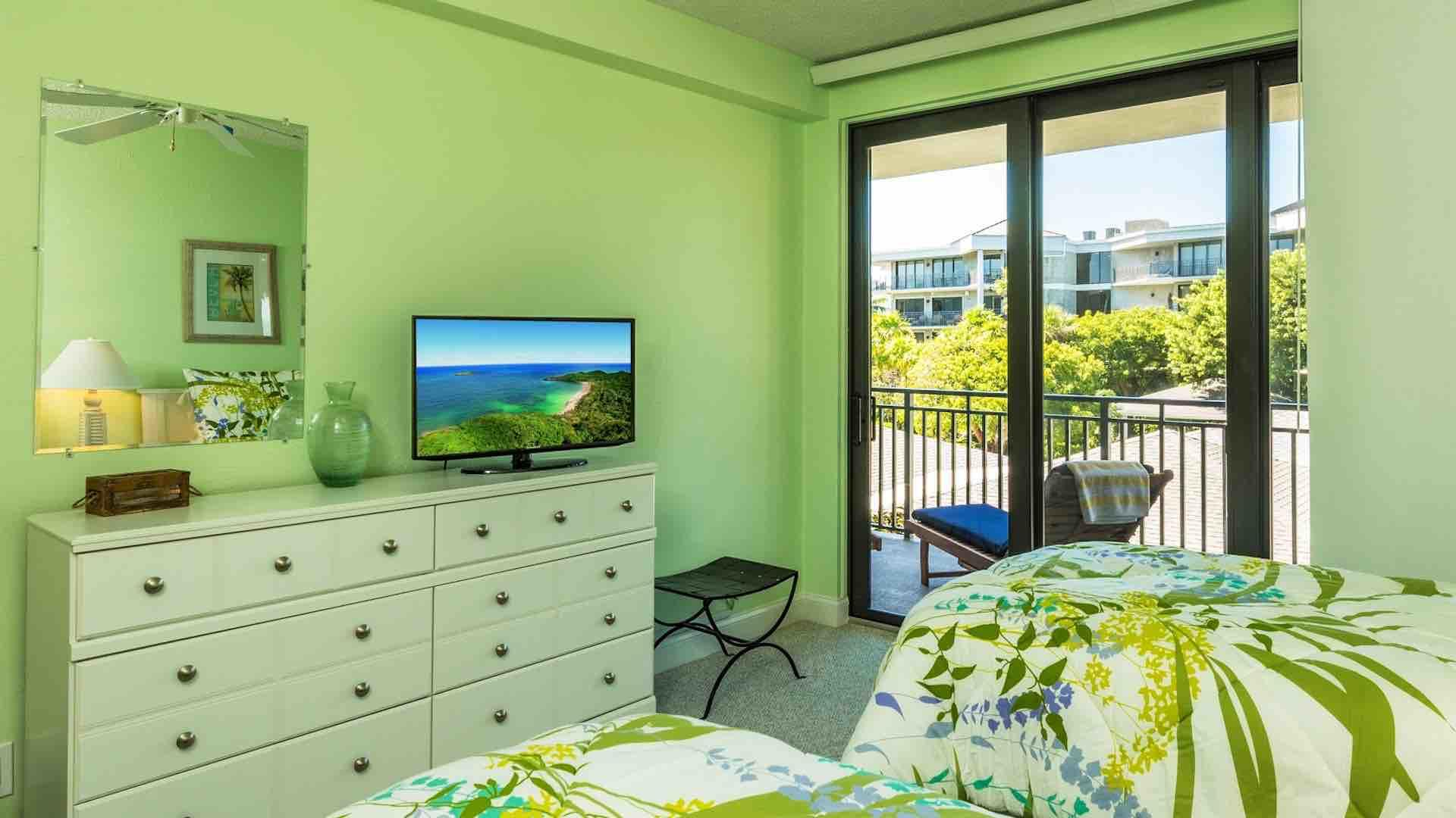 The elegantly furnished second bedroom has a flat screen TV and balcony access..