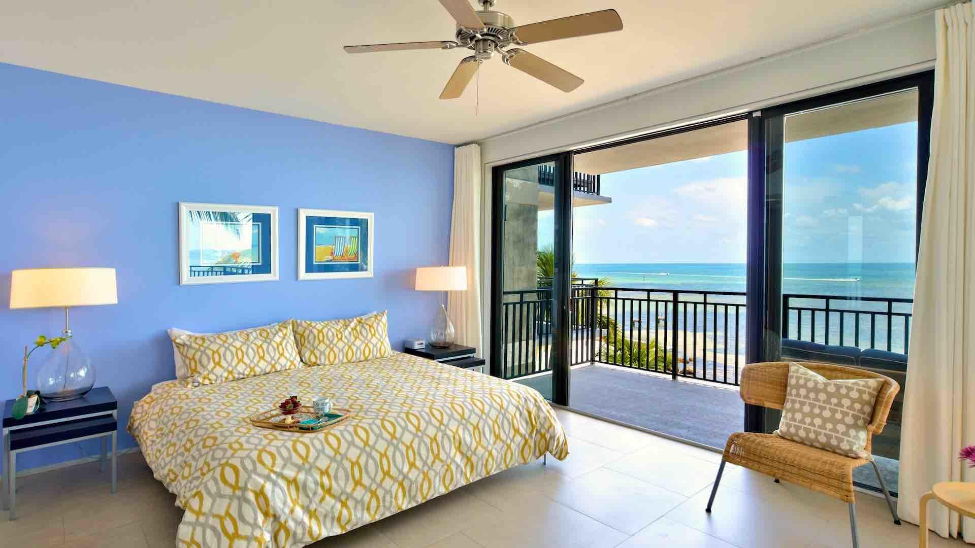 The master bedroom has a king bed and dramatic ocean views...