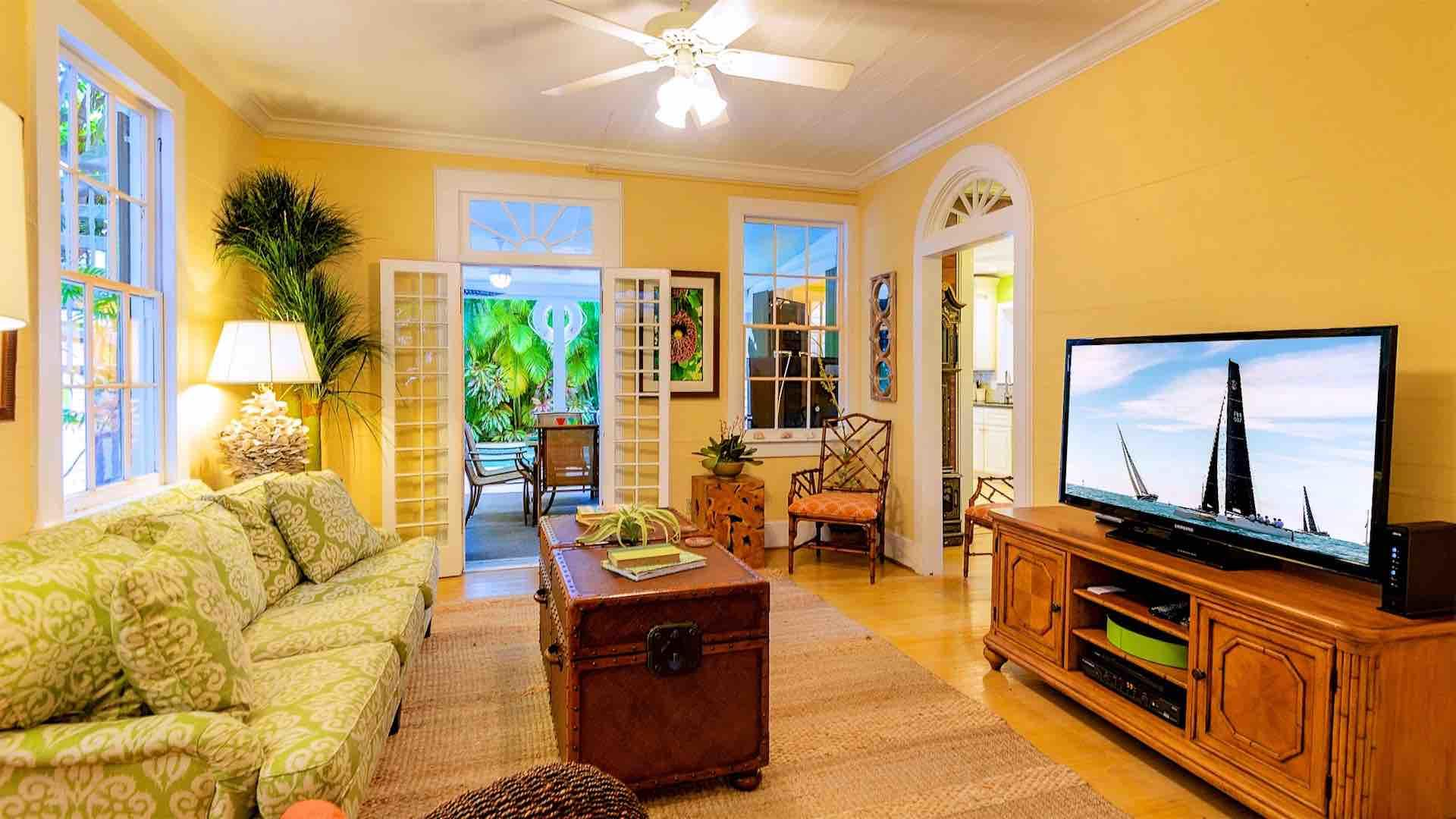 The living room features French doors on two sides, and a huge flat screen TV.