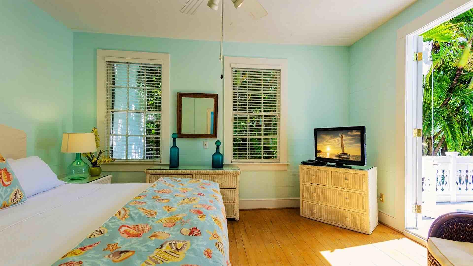 The second master suite has a king bed, overhead fan and flat screen TV.