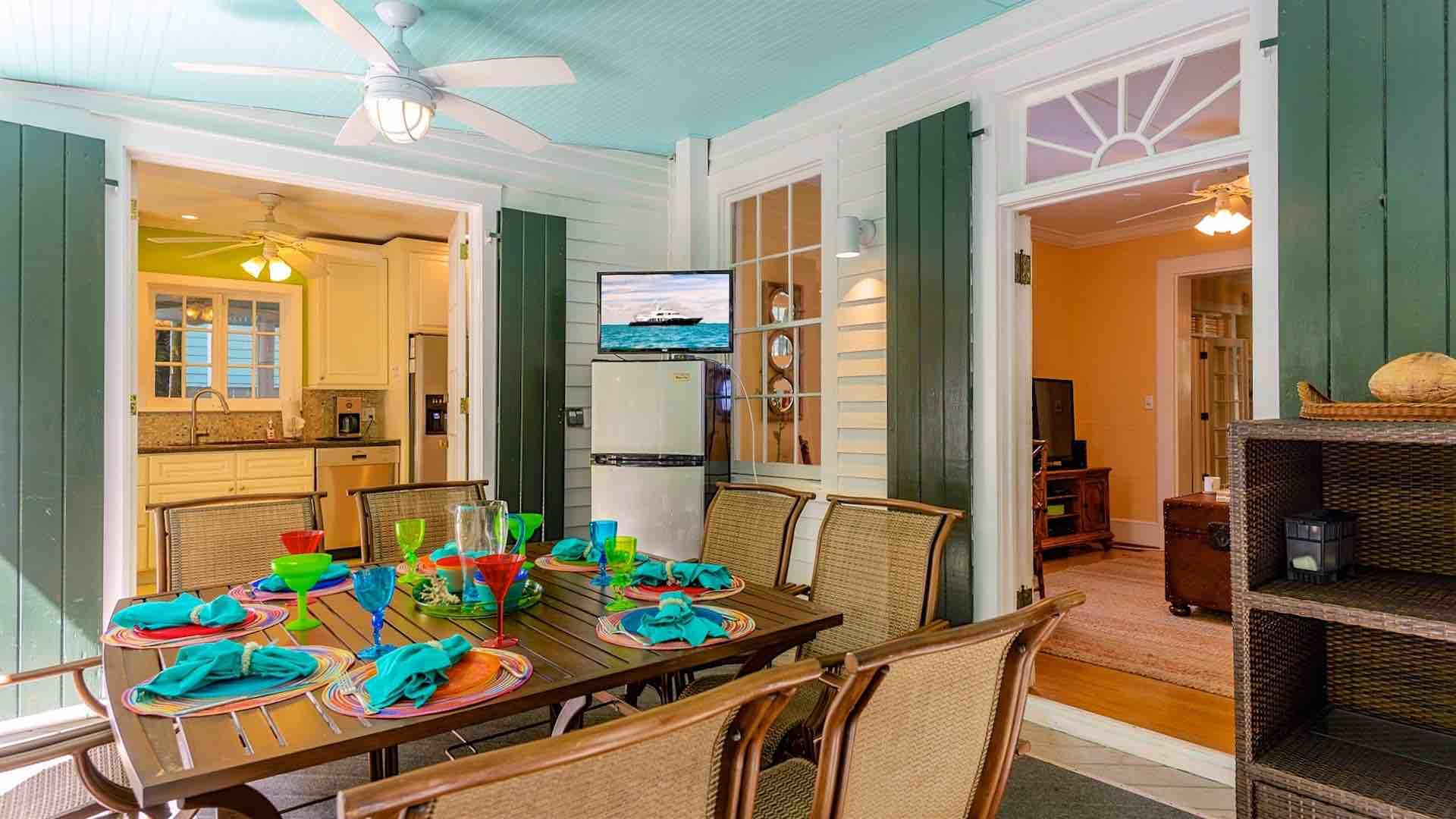 The back porch facing the pool area features a TV and dining table for eight.