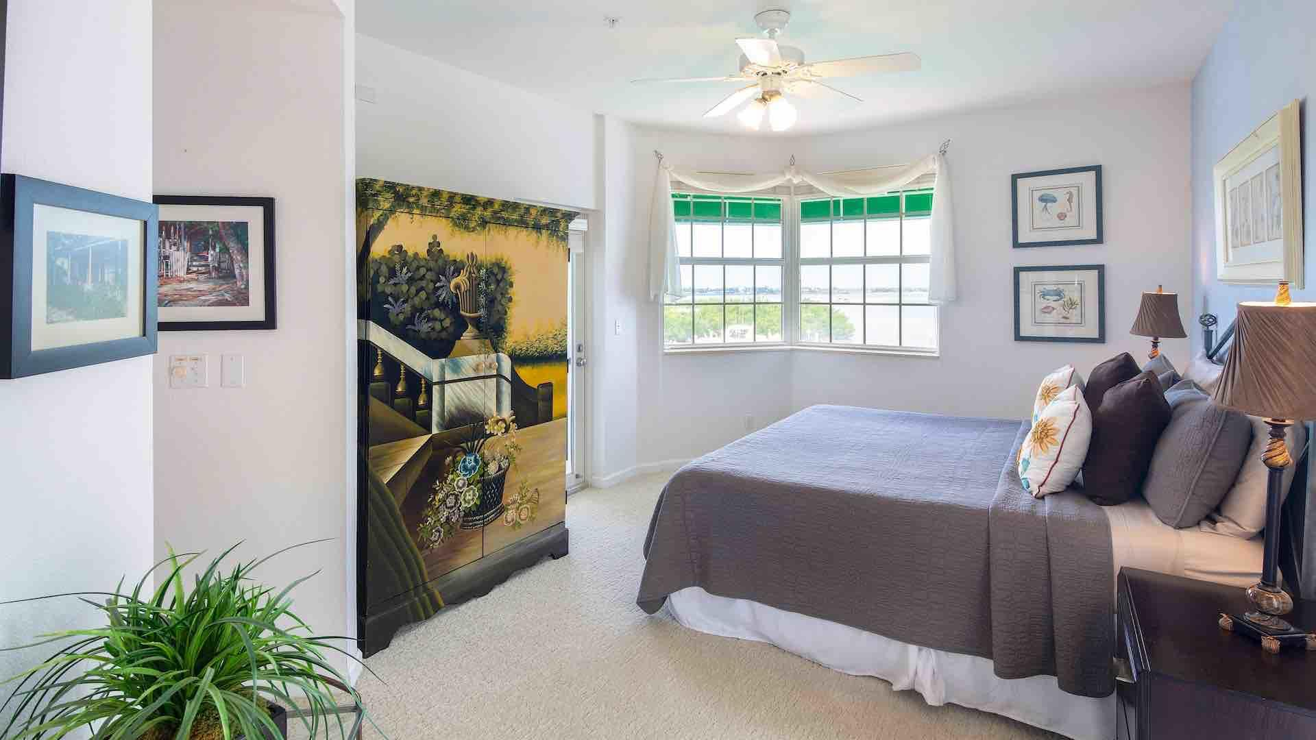 The master bedroom has an overhead fan and a large armoire with a flat screen TV...