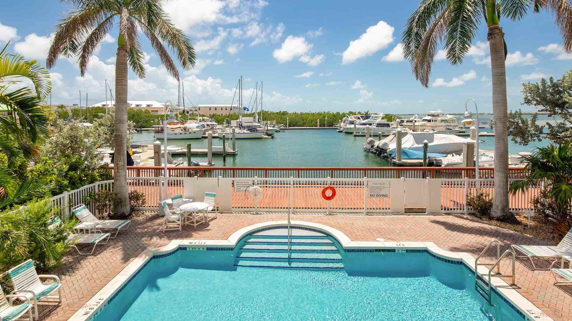 The pool faces the waterfront and is surrounded by chaise lounges...