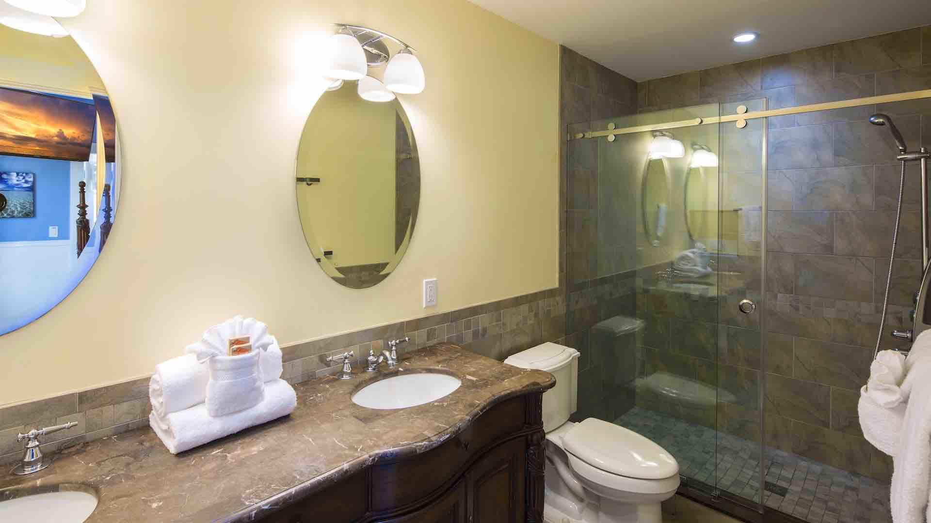 The master bathroom is en suite with twin vanities and a large glass shower...