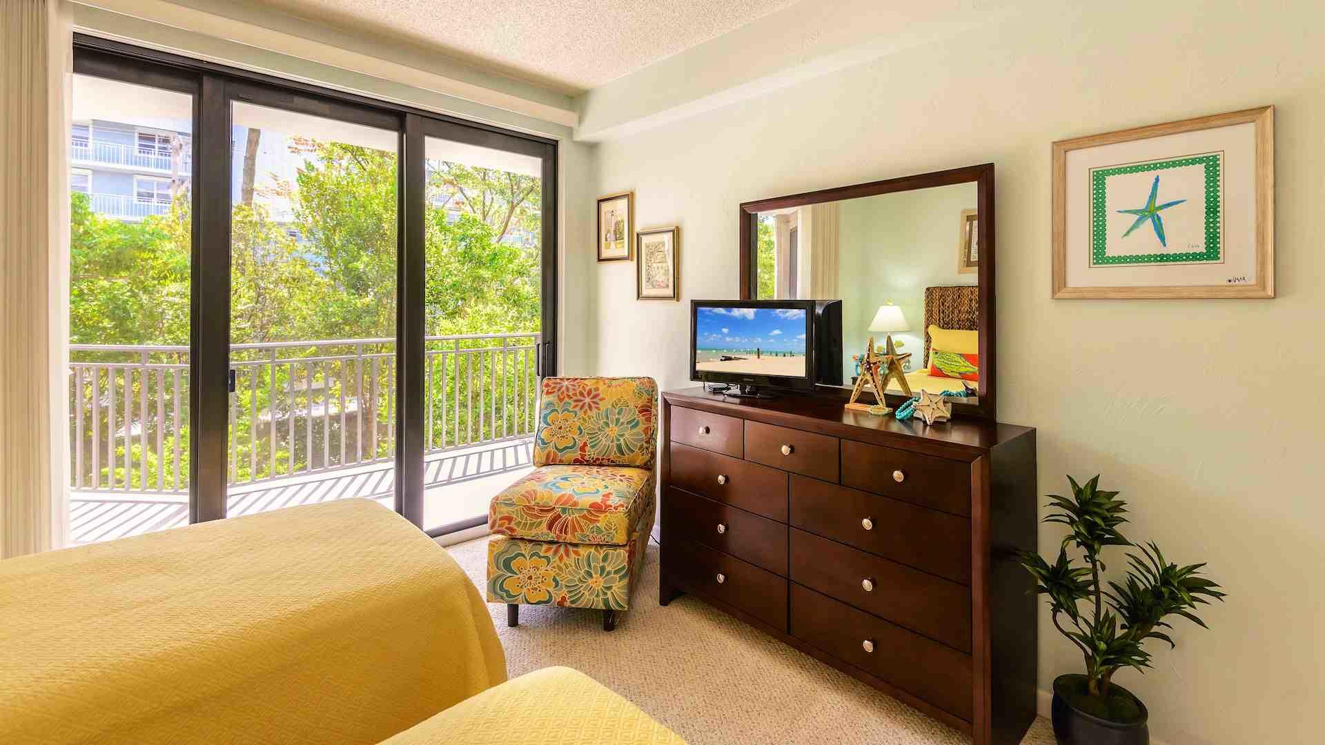 The second bedroom has triple sliders to the balcony , flat screen TV & dresser.