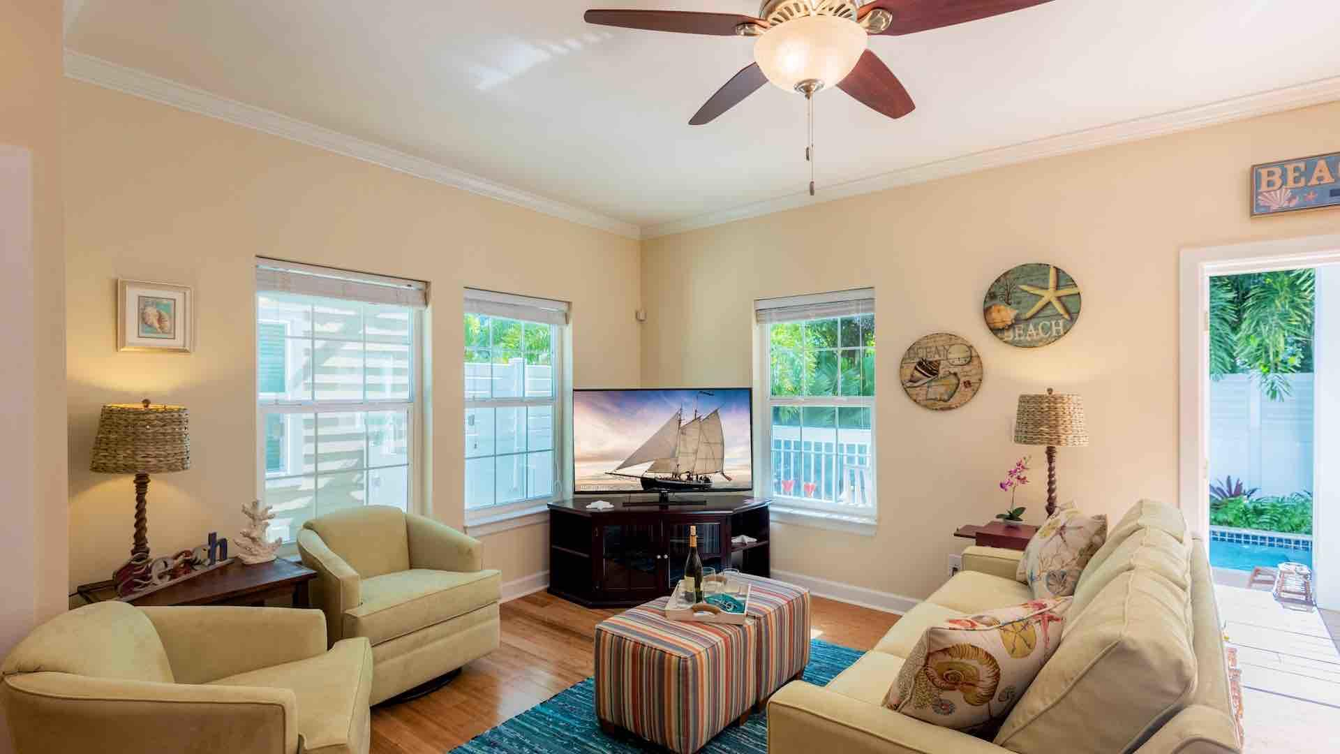 The elegant tropical living area has a flat screen TV and plenty of seating...