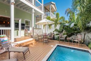 The fully fenced private back pool area with chaise lounges and outdoor dining..