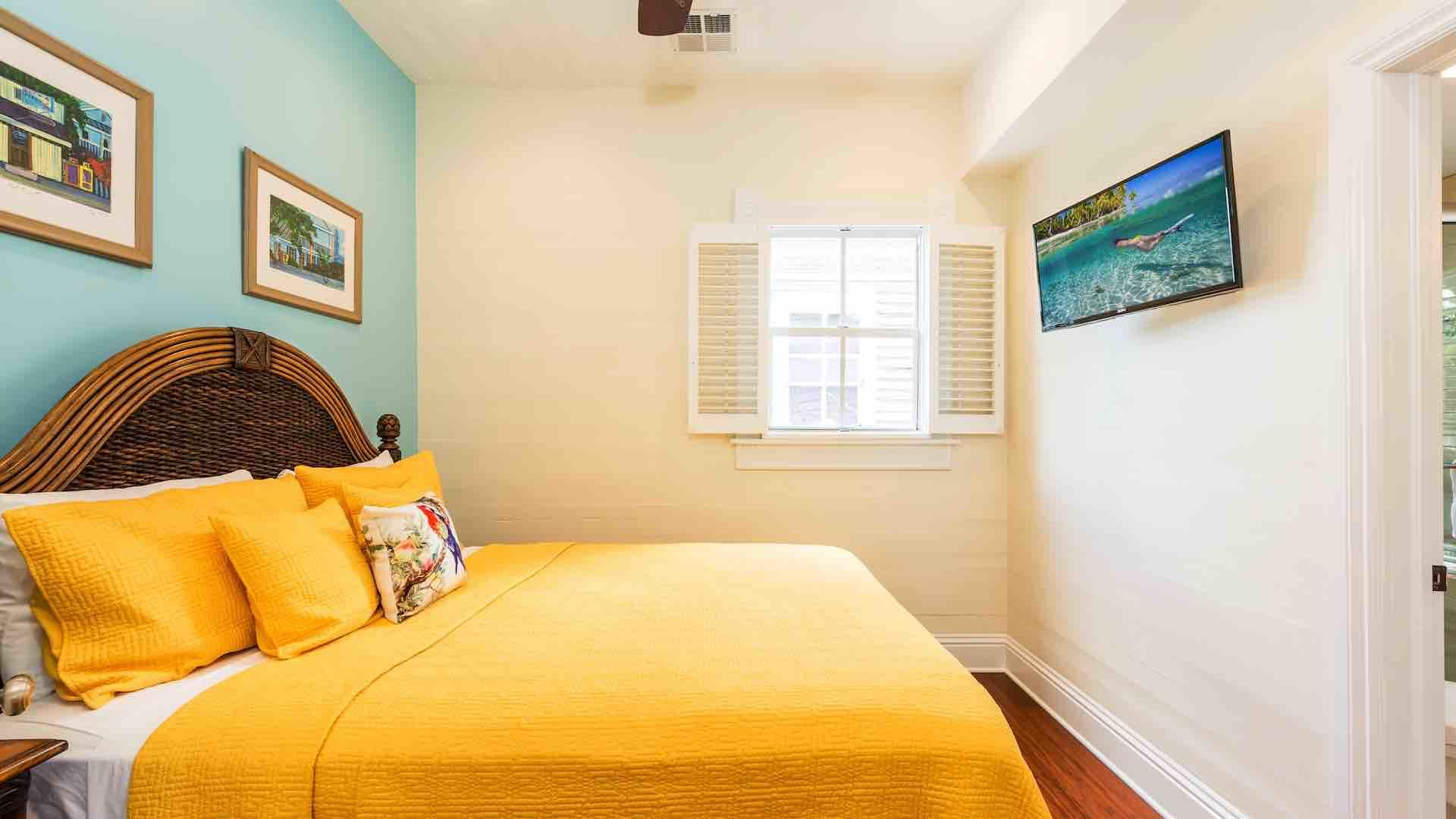 The master bedroom has a Queen bed, an overhead fan, and a flat screen TV...