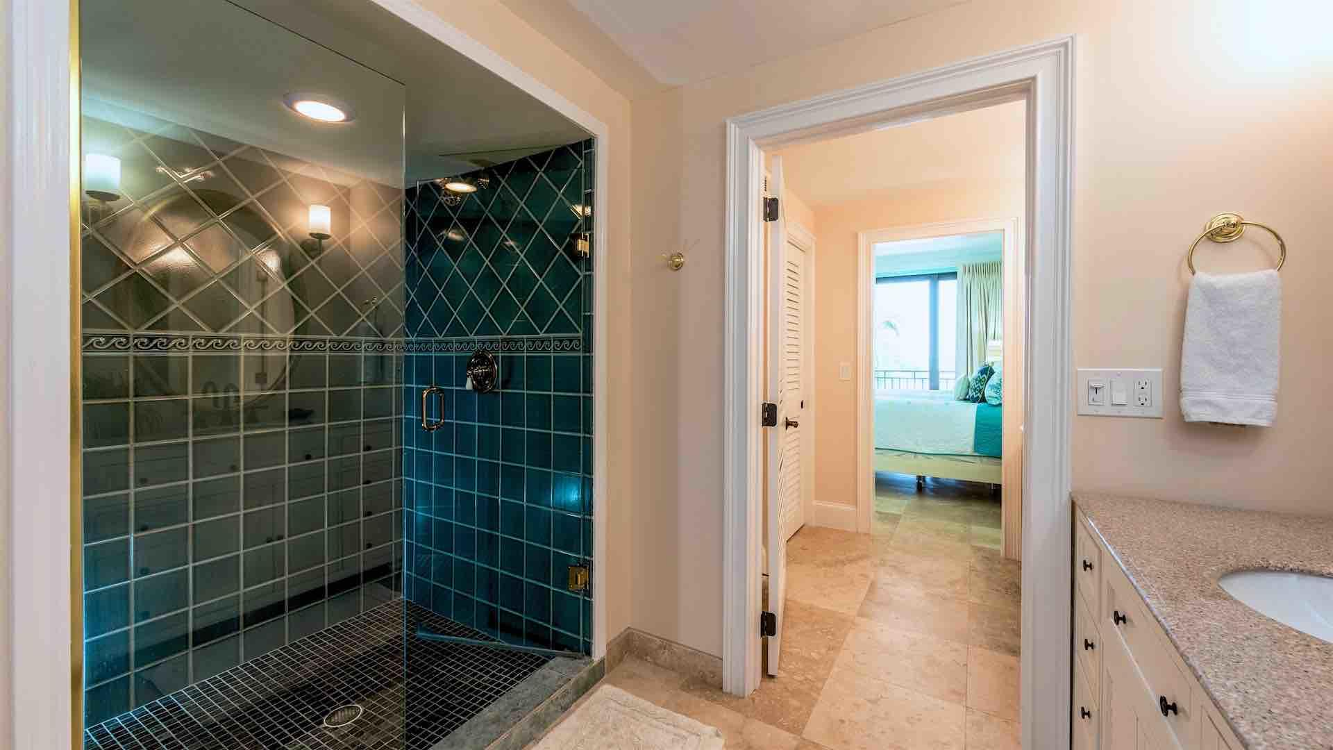 The master bathroom has a large glass shower...
