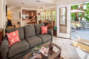 The living room has plenty of seating and opens up to a private deck...