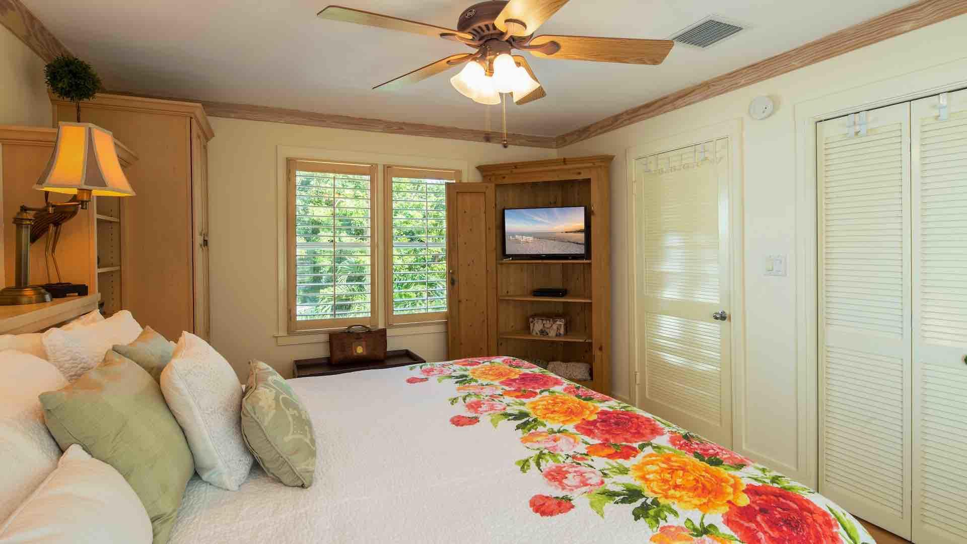 The master bedroom has an overhead fan and flat screen TV...