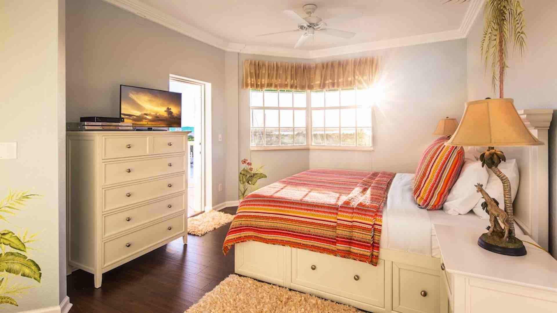 The master bedroom has a King bed, flat screen TV, and balcony access...