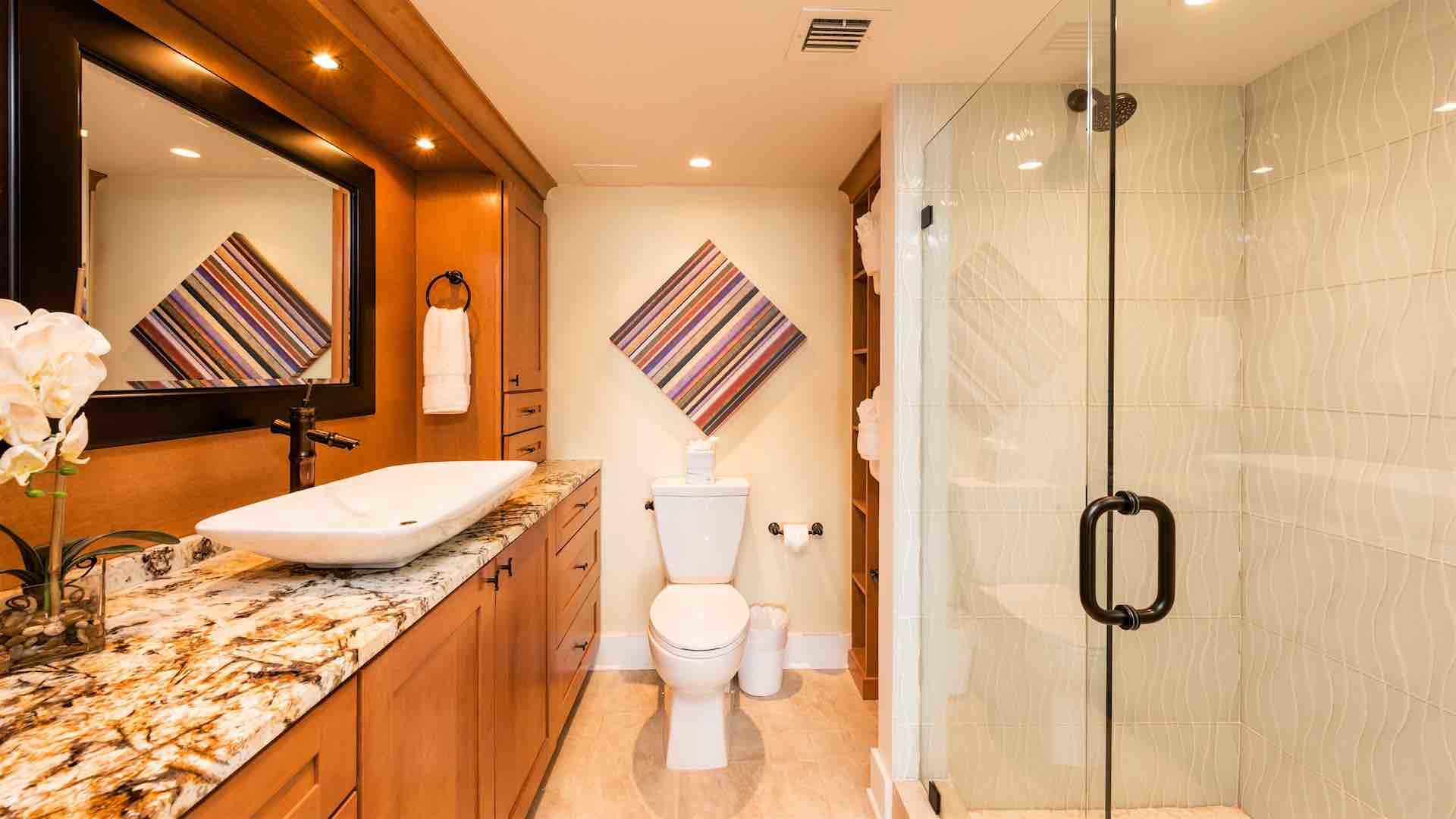 The en suite master bathroom has a large glass shower...