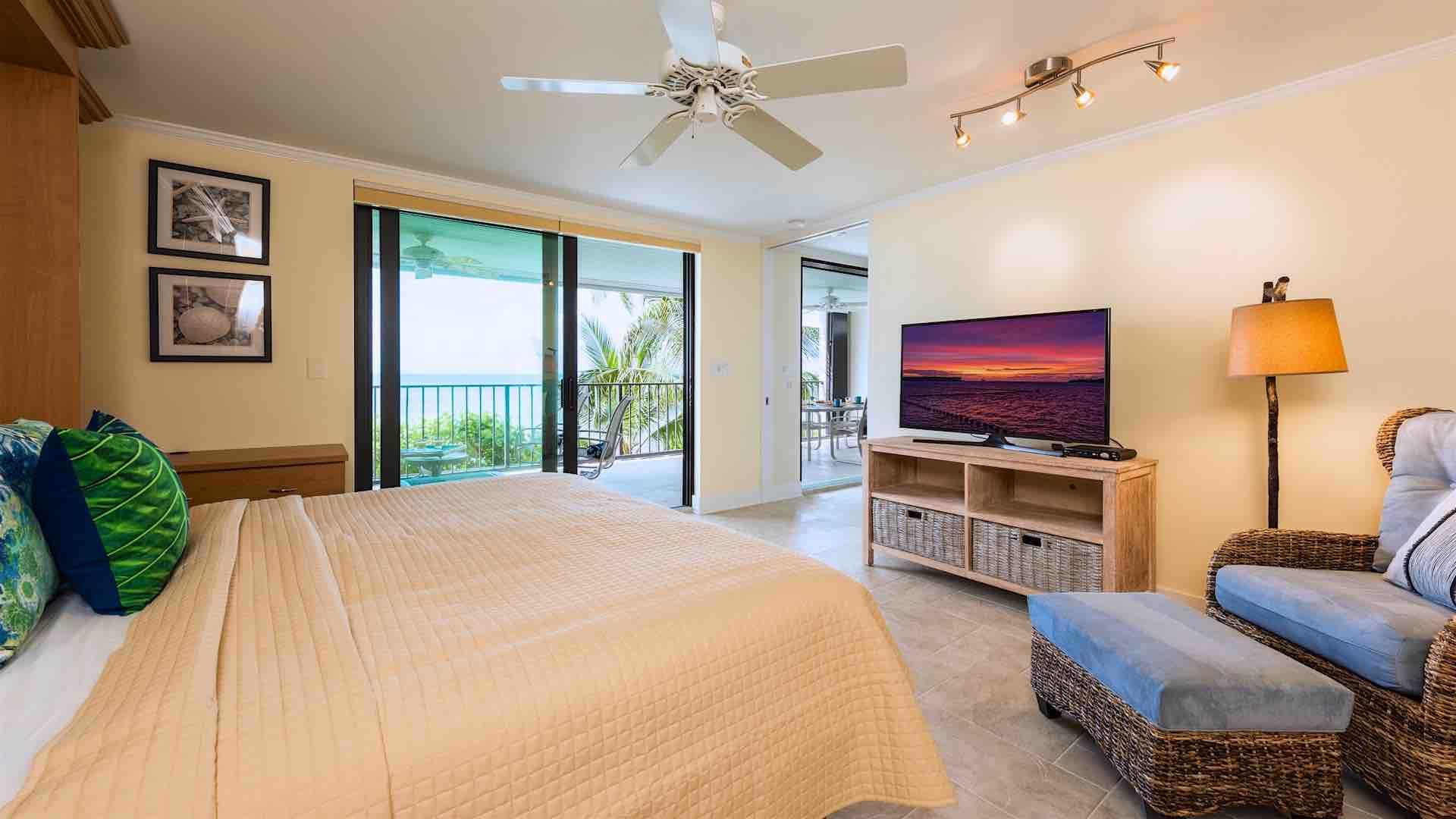 The master bedroom has a large flat screen TV and balcony access...