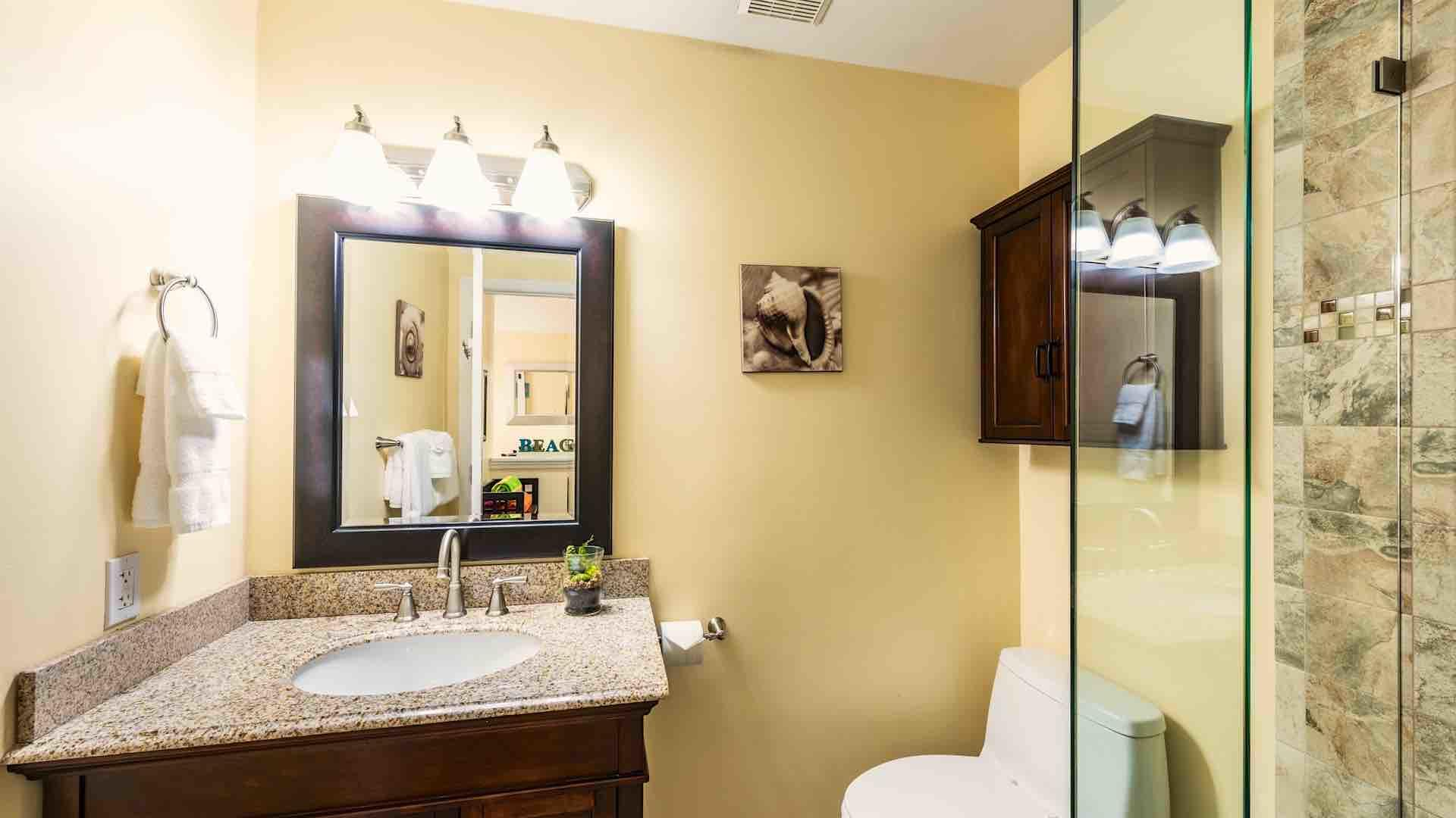 The bathroom is located in the hall between the two bedrooms...