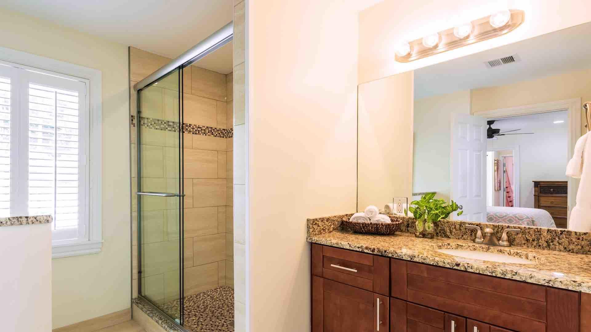The downstairs master bathroom has a walk-in glass shower...