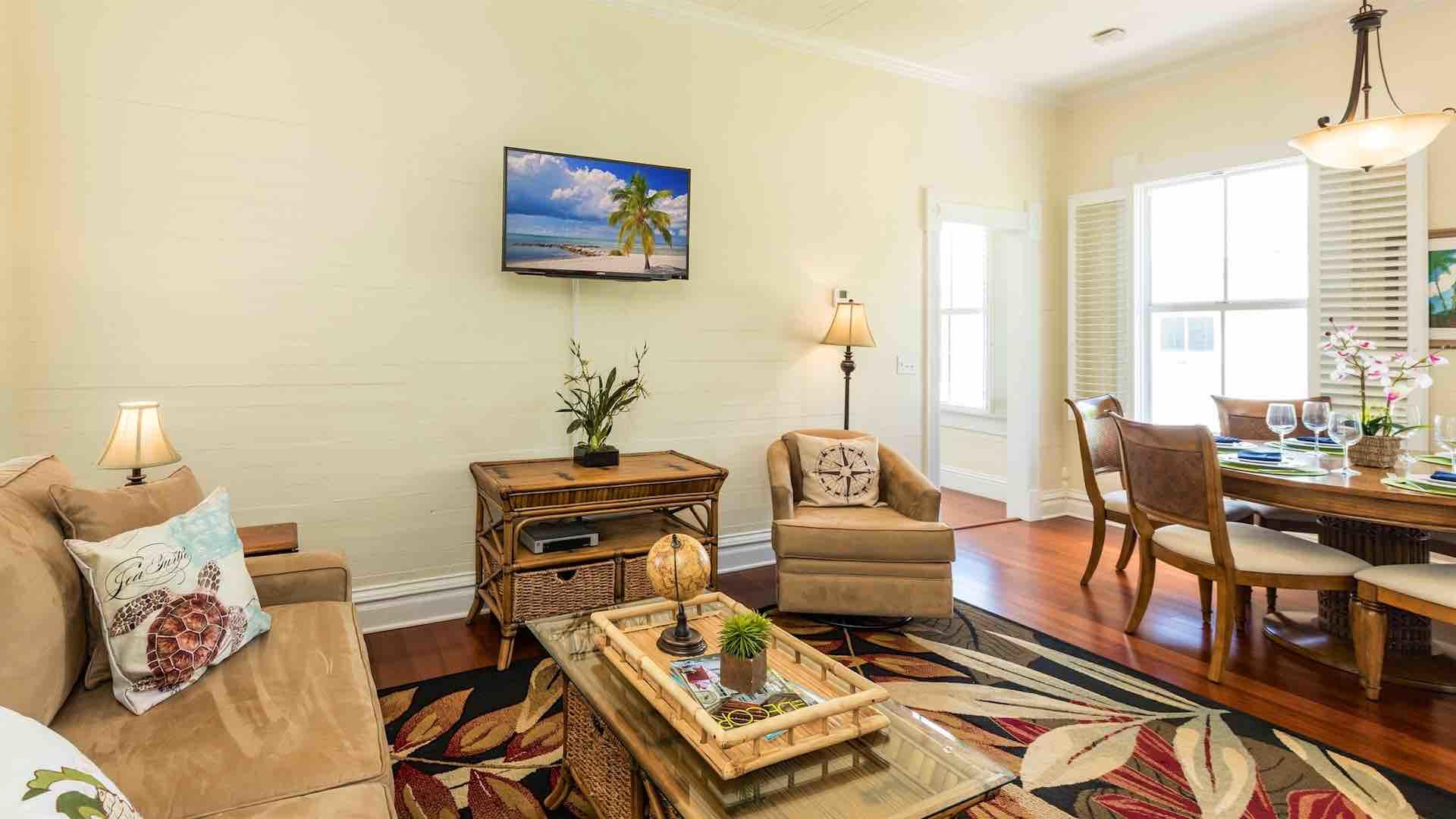 The upstairs condo has a spacious living area, with a large flat screen TV...