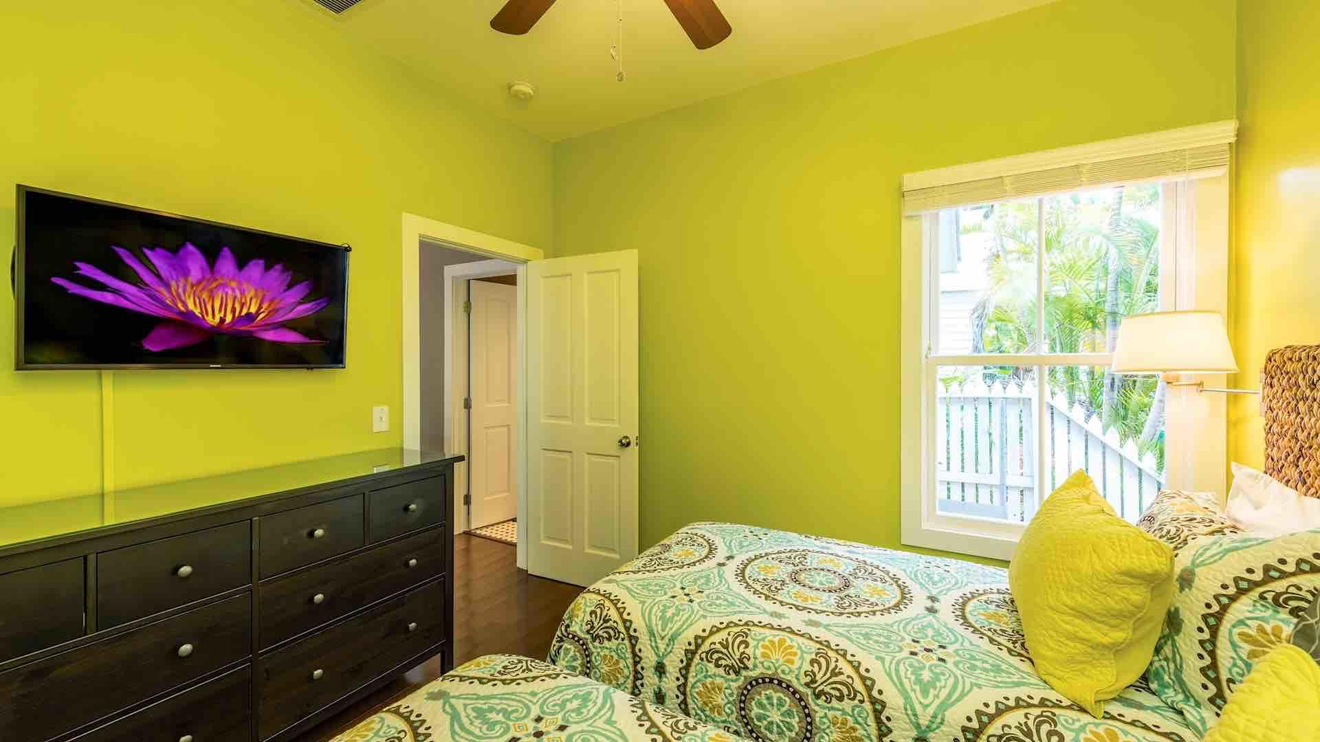 The guest bedroom has a large mounted flat screen TV...