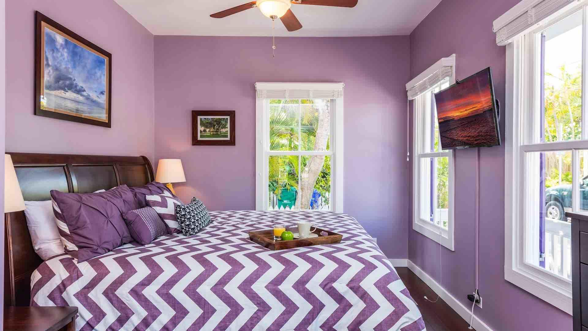 The master bedroom has an overhead fan and large flat screen TV...