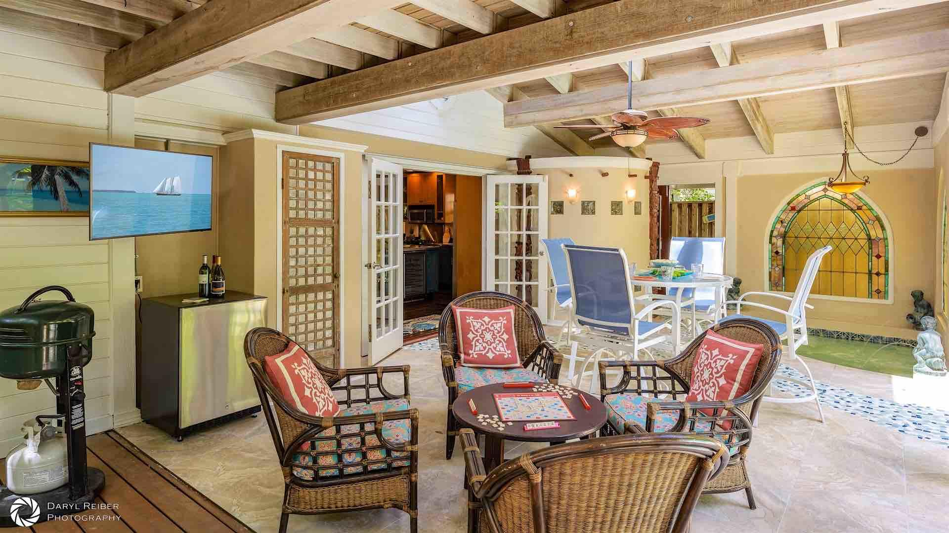 The covered lanai has both outdoor dining and seating areas and a flat screen TV...