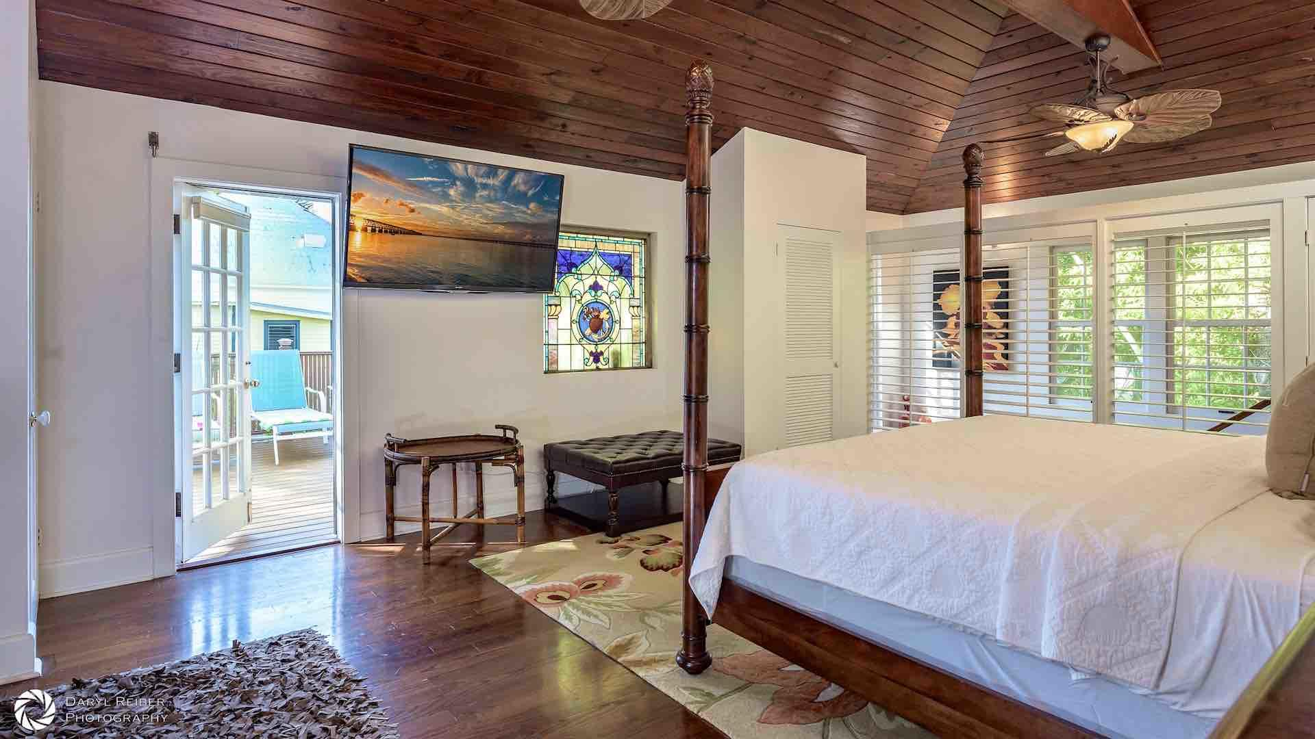 The master bedroom has a large mounted flat screen TV and two overhead fans...