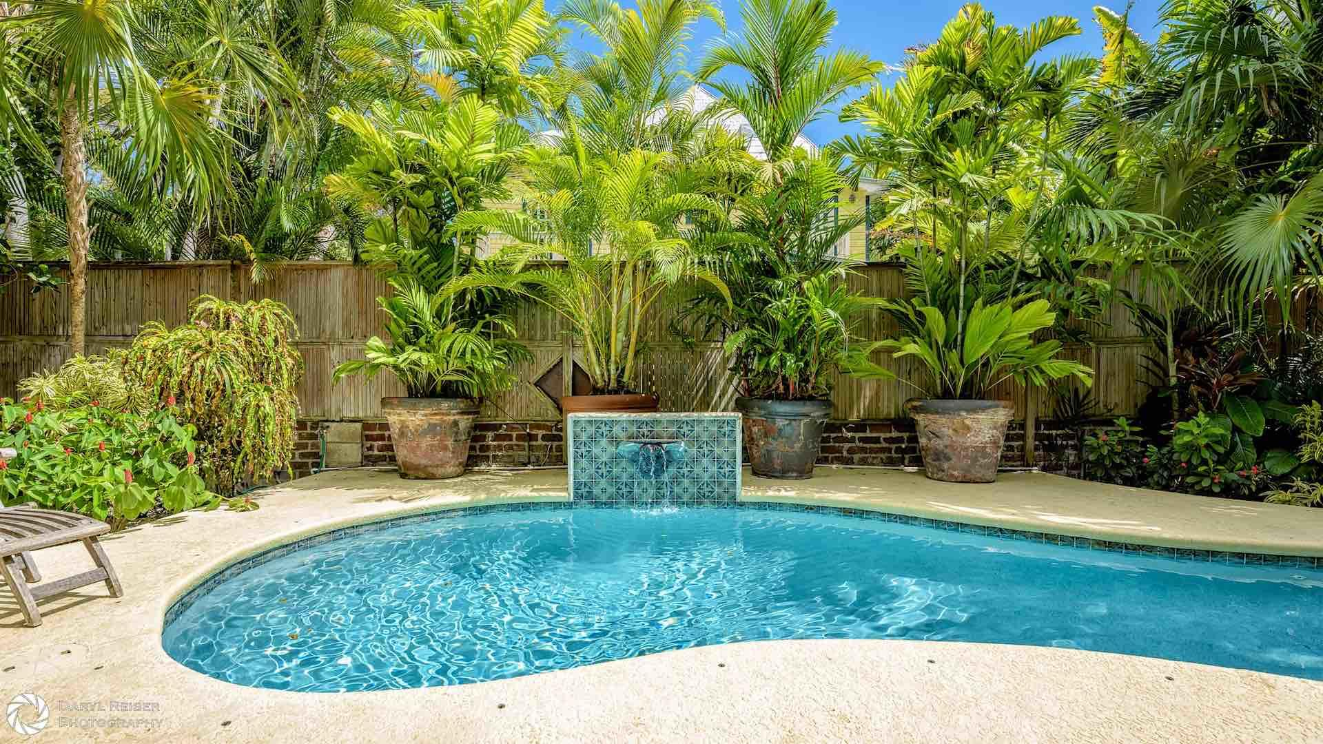 The private heated pool is surrounded by lush greenery...