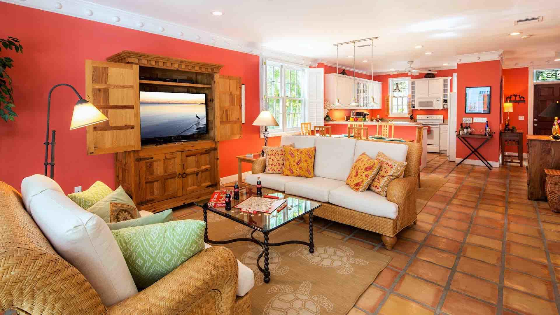 The living room has a large flat screen TV and plenty of comfortable beachy seating...